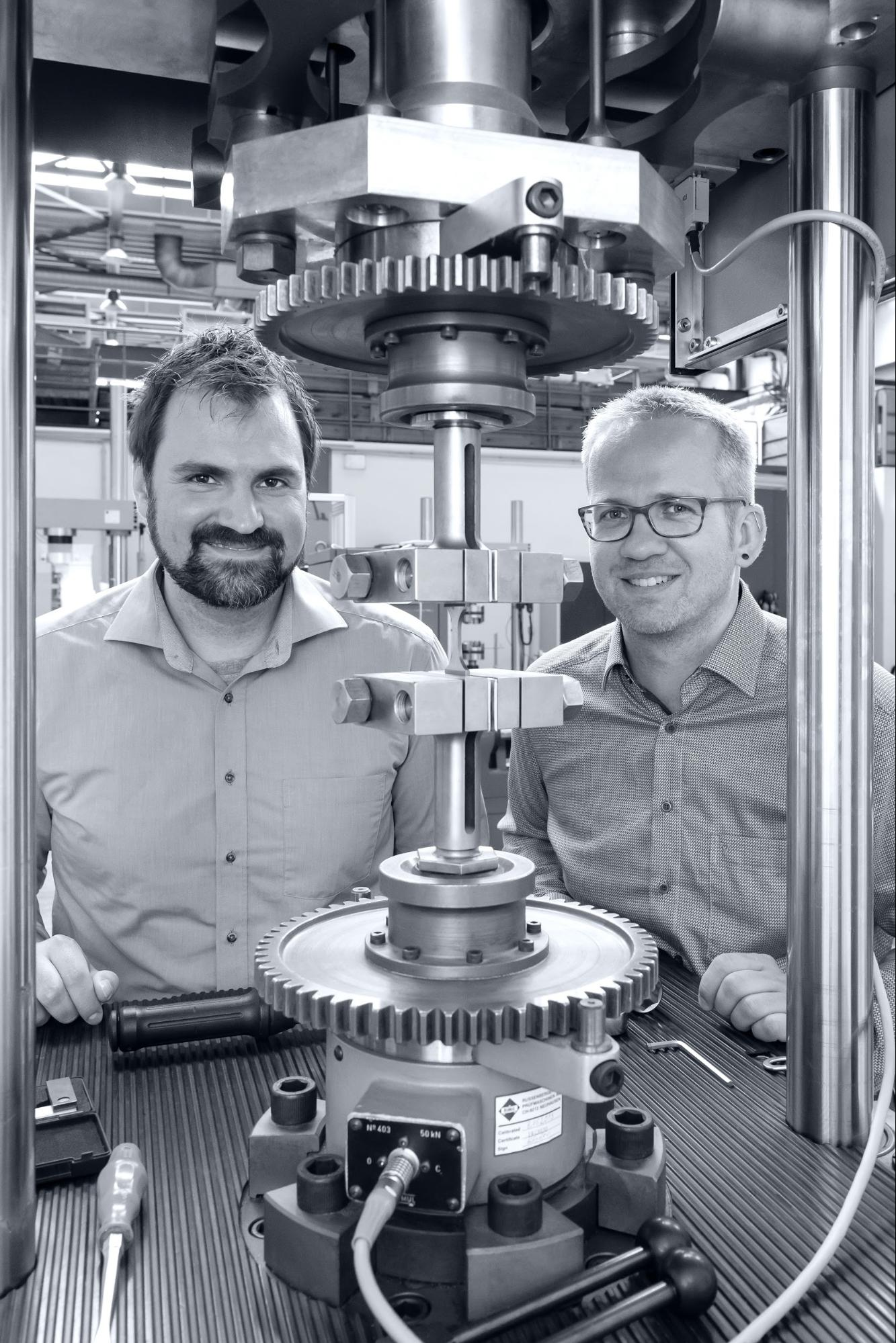 Dr. Nils Ellendt and Sebastian Huhn stand next to the fatigue testing machine